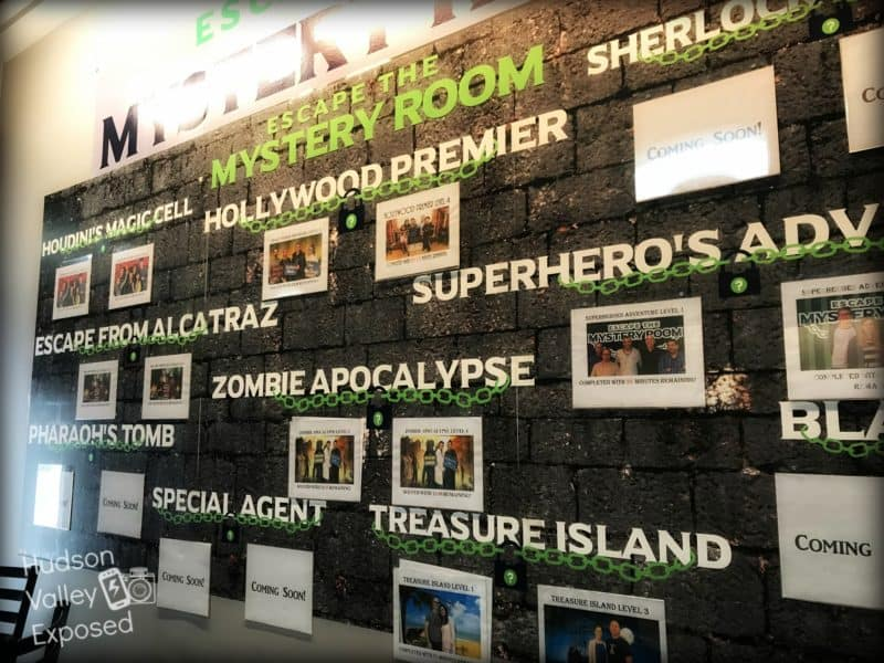 The wall of all the scenarios at the Palisades Mall Mystery Room
