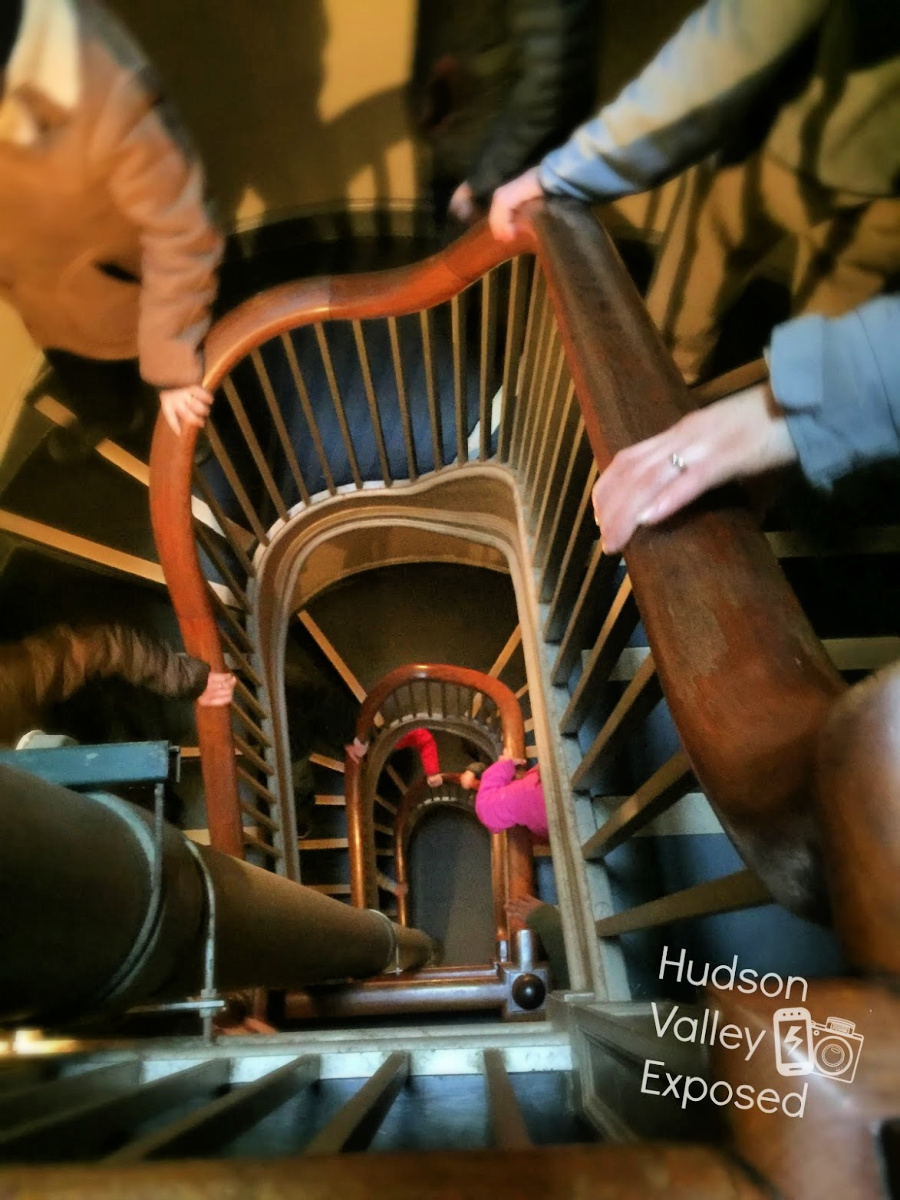 Hands on railing of back staircase of one of the glorious Vanderbilt Homes