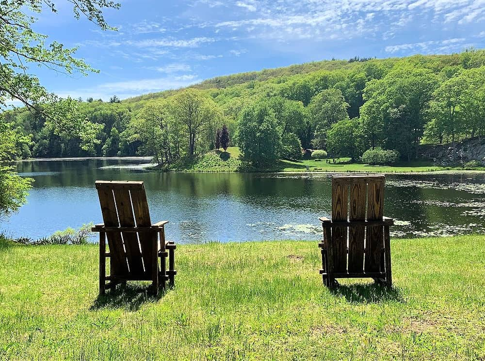 Two chairs facing the lake at this pristine Millbrook garden