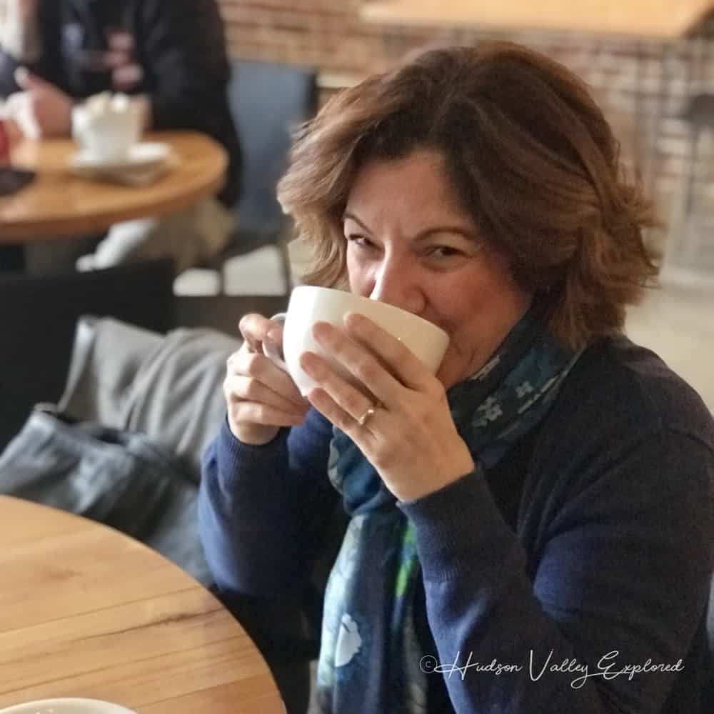 Jackie from Hudson Valley Explored drinking coffee. This Hudson Valley Blog is your best bet for finding things to do in the HV