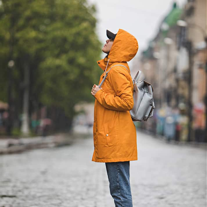 Girl in raincoat and backpack looking up